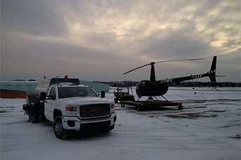 Company Training at L R Helicopters. - a truck and a helicopter standing side by side