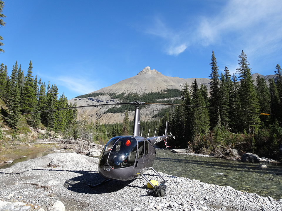 Enviromental and parks government service - Helicopter on top of a mountain