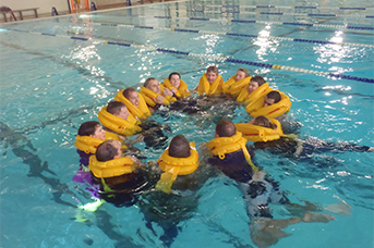 Company Training Program - A group of people inside a pool holding hands on a helicopter safety training.